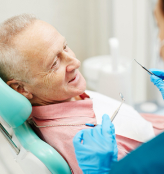 An older man having his teeth checked by the dentist