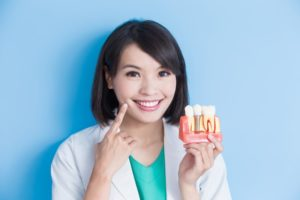Smiling Burleson dentist holding model jaw with dental implant