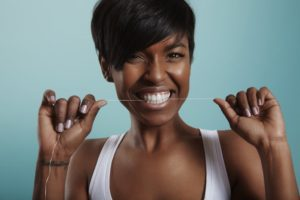 Woman flossing as recommended by Burleson dentist