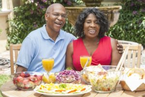 couple with dental implants in Burleson enjoying assorted summer foods