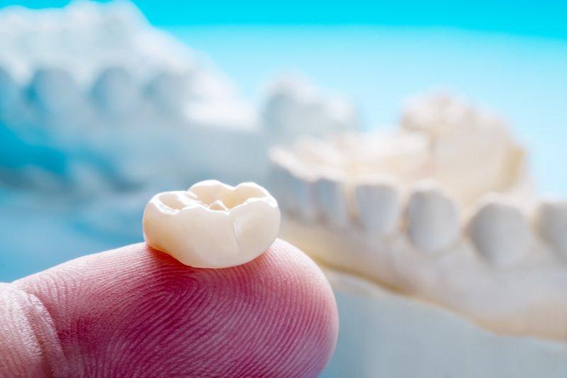 person holding dental crown on fingertip